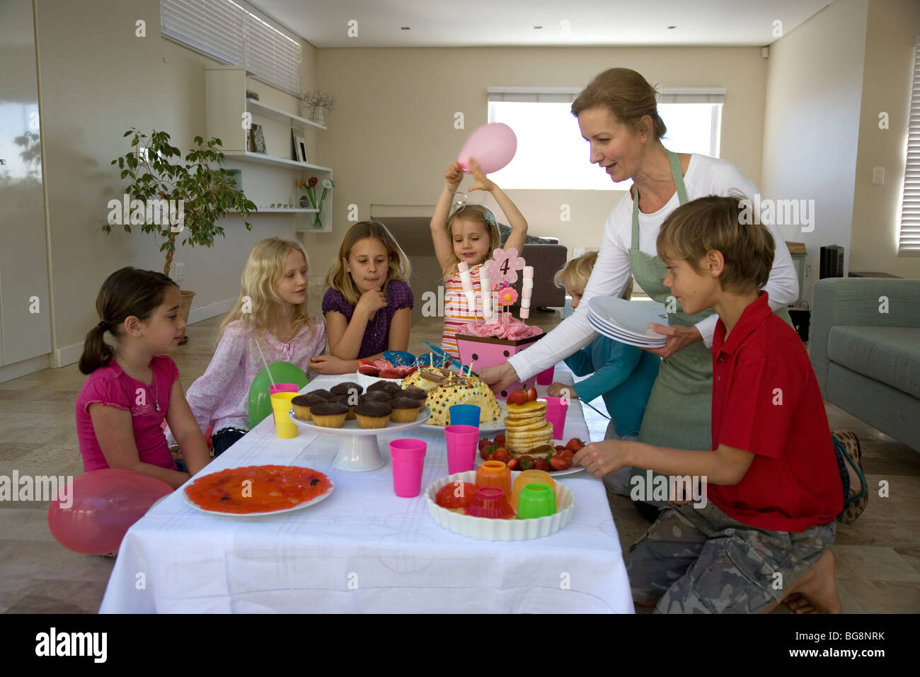 small childrens kids around table with sweets and cakes - Small Childrens Images