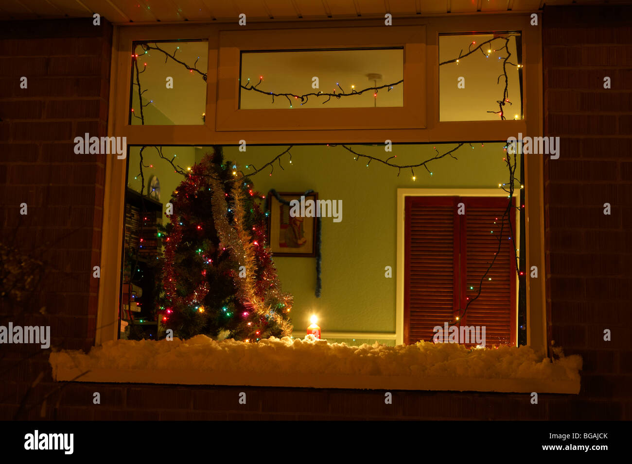 Candle burning in the window of a house with christmas