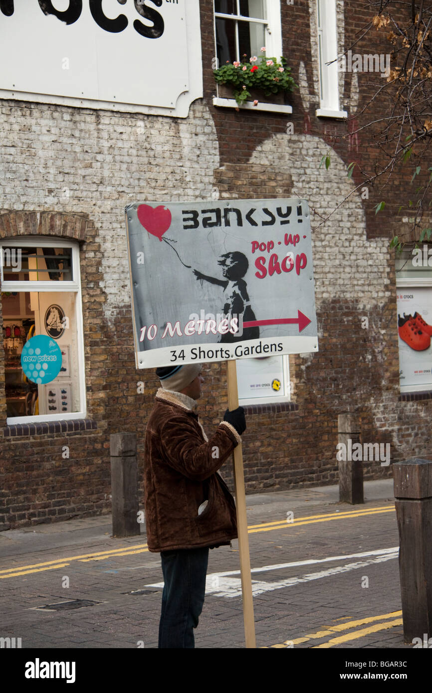 Man holding a Banksy pop up shop sign, Covent Garden, London Stock ...