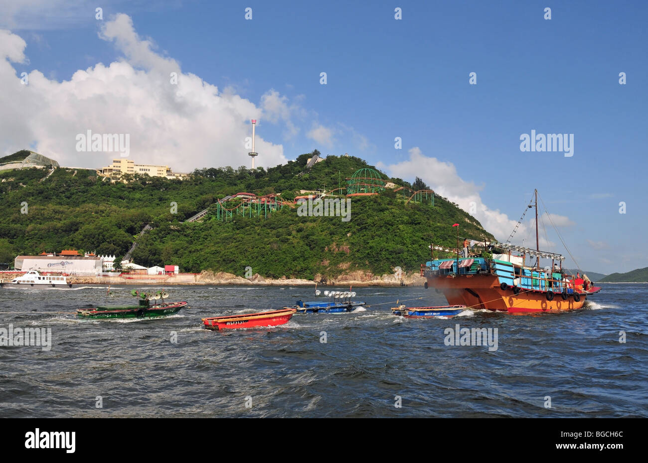 Side view of a fishing junk, towing small boats, in the open sea ...