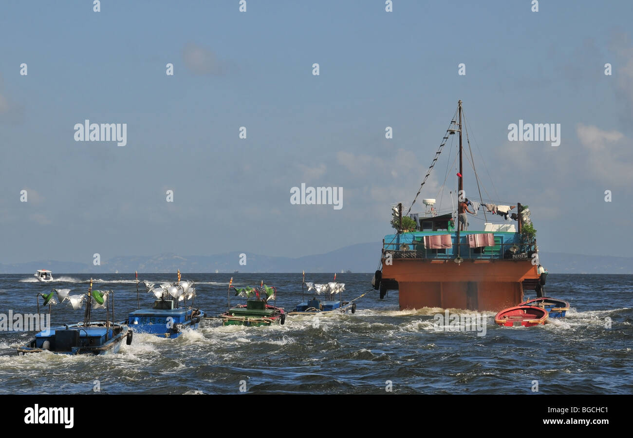 Stern view of a fishing junk houseboat towing two lines of small ...
