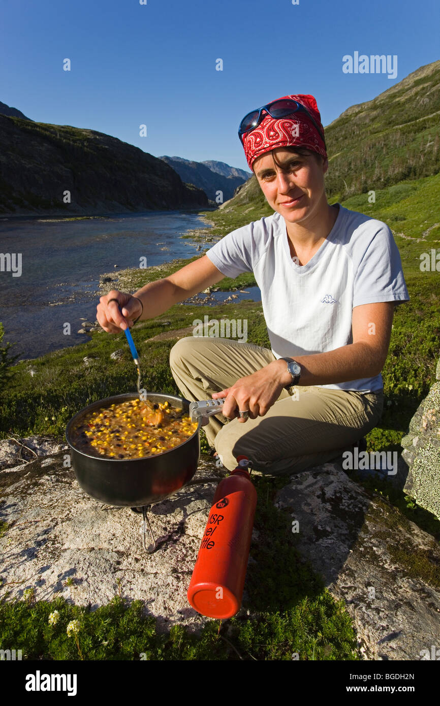 Young woman preparing a meal cooking outdoors msr fuel for Meal outdoors