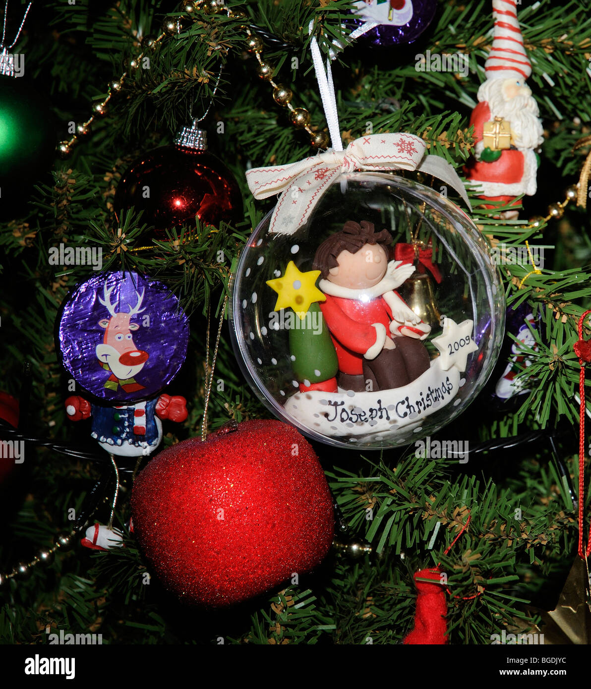 A personalised Christmas bauble containing a handcrafted figure of ...