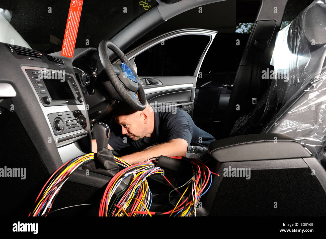 Automotive Wiring Harness Uk : A fitter putting wiring loom harness in skoda