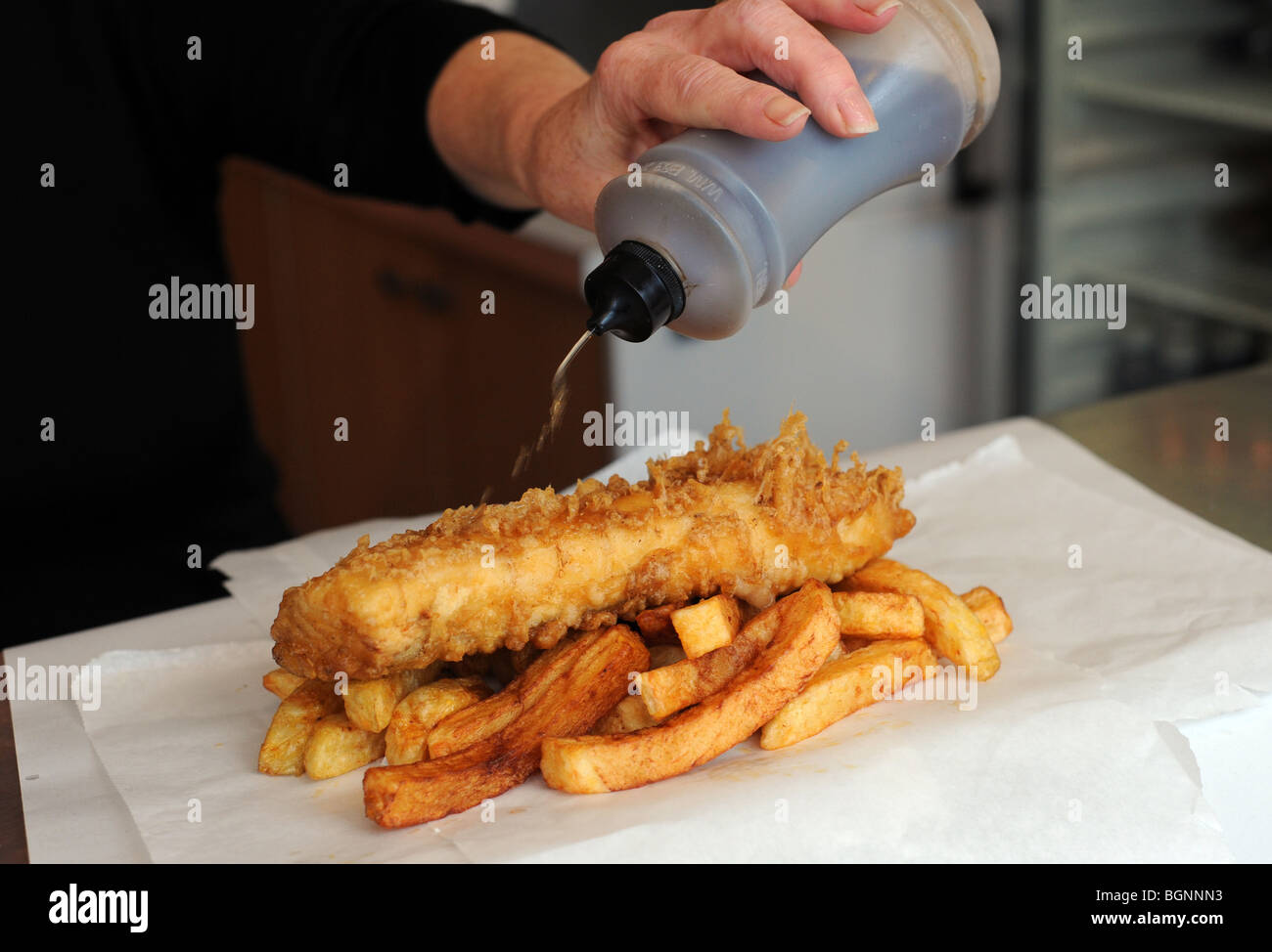 putting vinegar on fish and chips stock photo royalty
