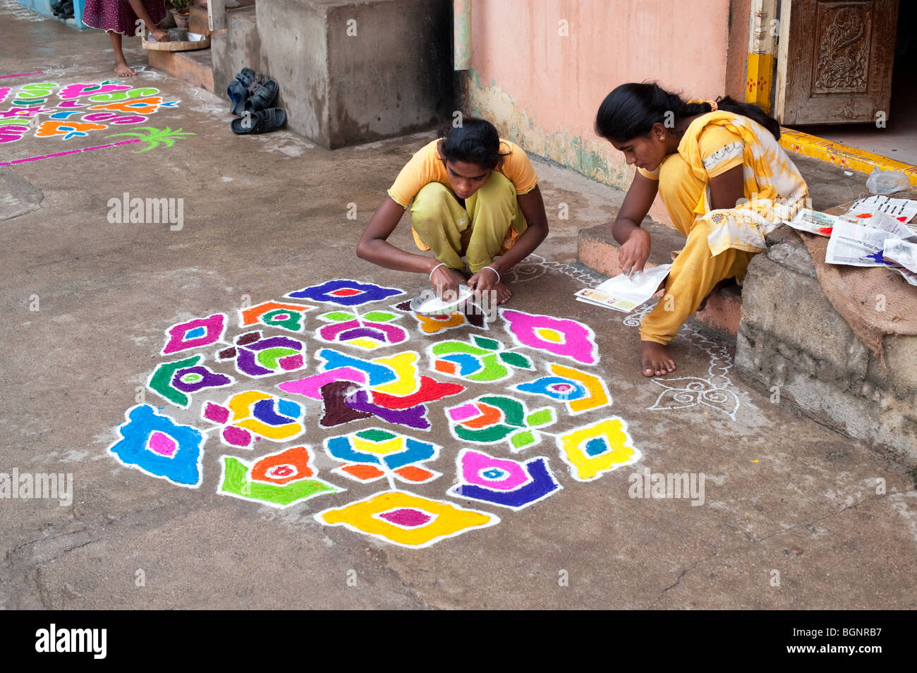 Indian Sisters Making A Rangoli Design Outside There Home During The Hindu  Festival Of Sankranti. Puttaparthi, Andhra Pradesh, India