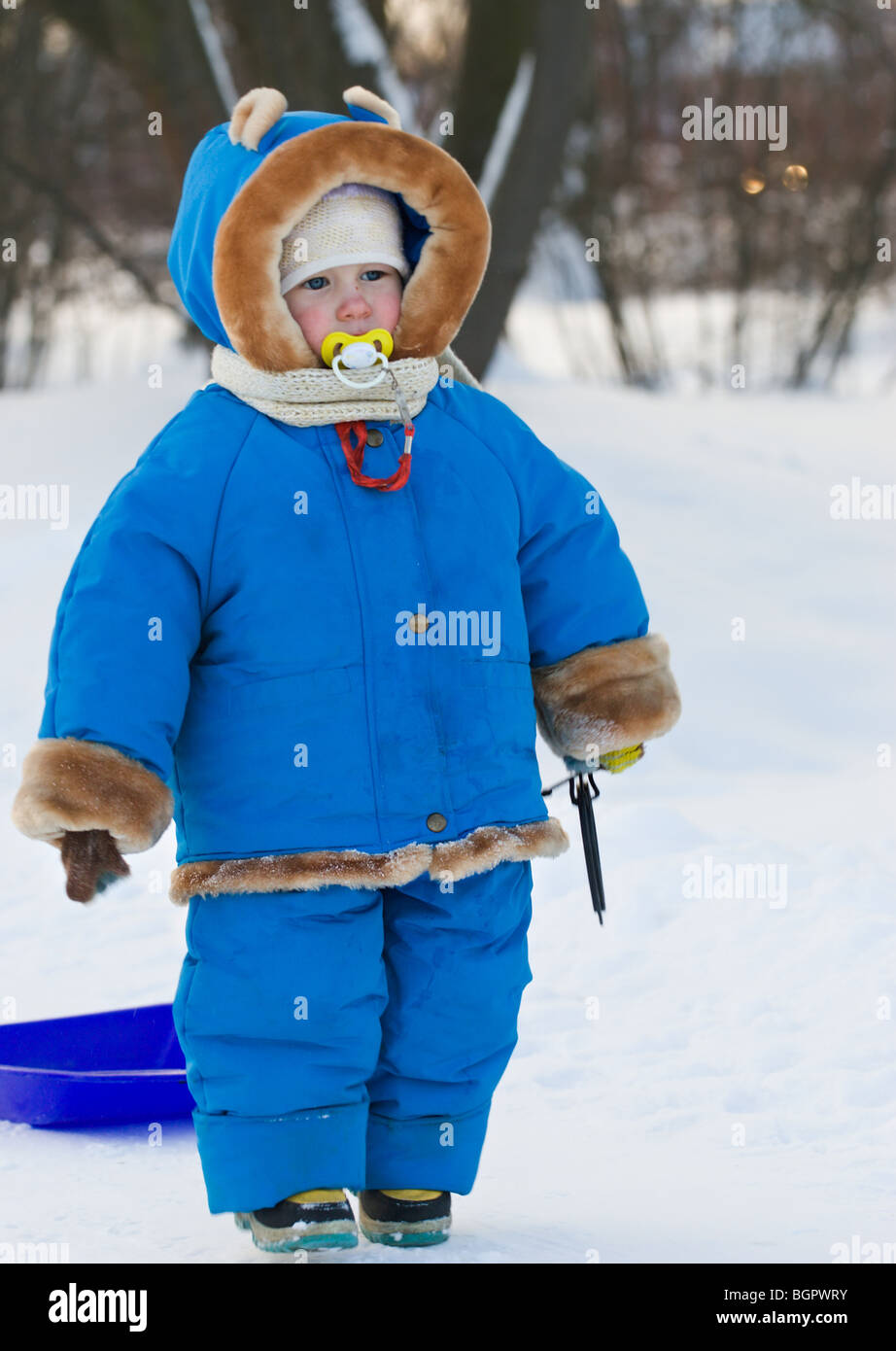 funny little child with nipple in mouth in blue winter warm ...