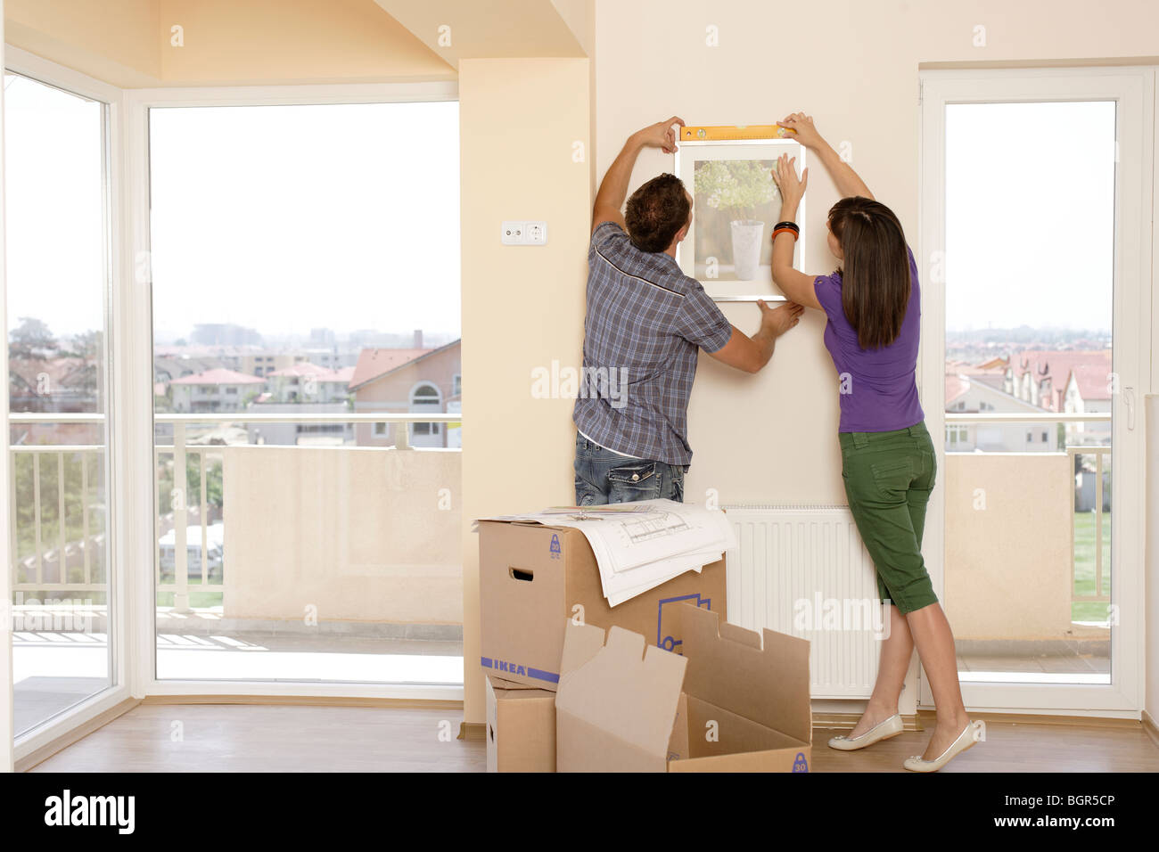 man and woman just moving in decorating a new apartment
