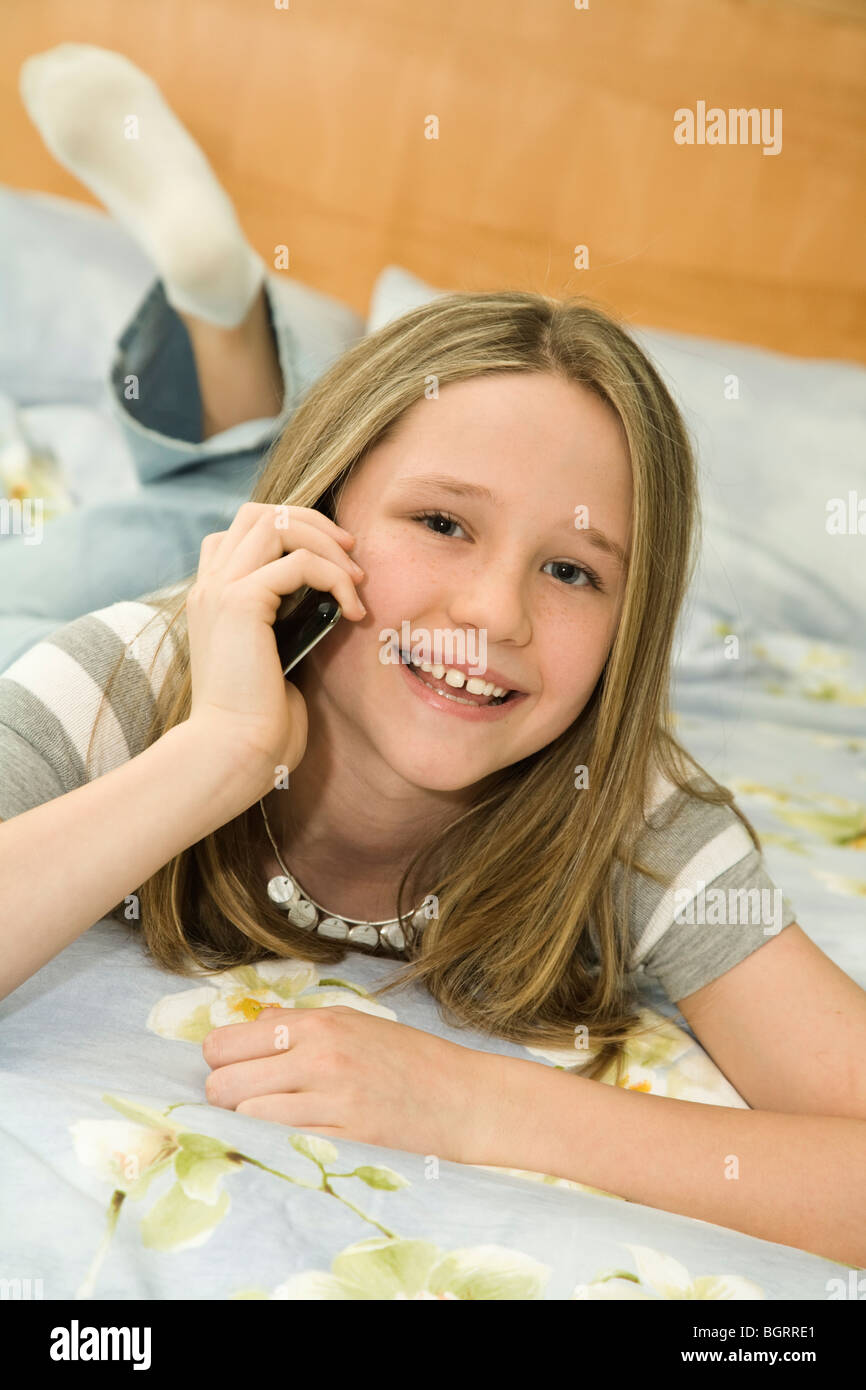 caucasian preteen girl laying in bed talking on a cell phone stock photo royalty free image. Black Bedroom Furniture Sets. Home Design Ideas