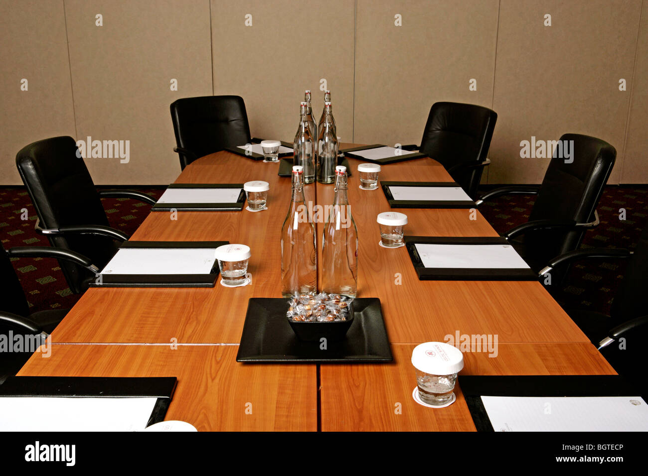 Conference room tables set for a meeting complete with water glasses pads and notepaper & Conference room tables set for a meeting complete with water ...
