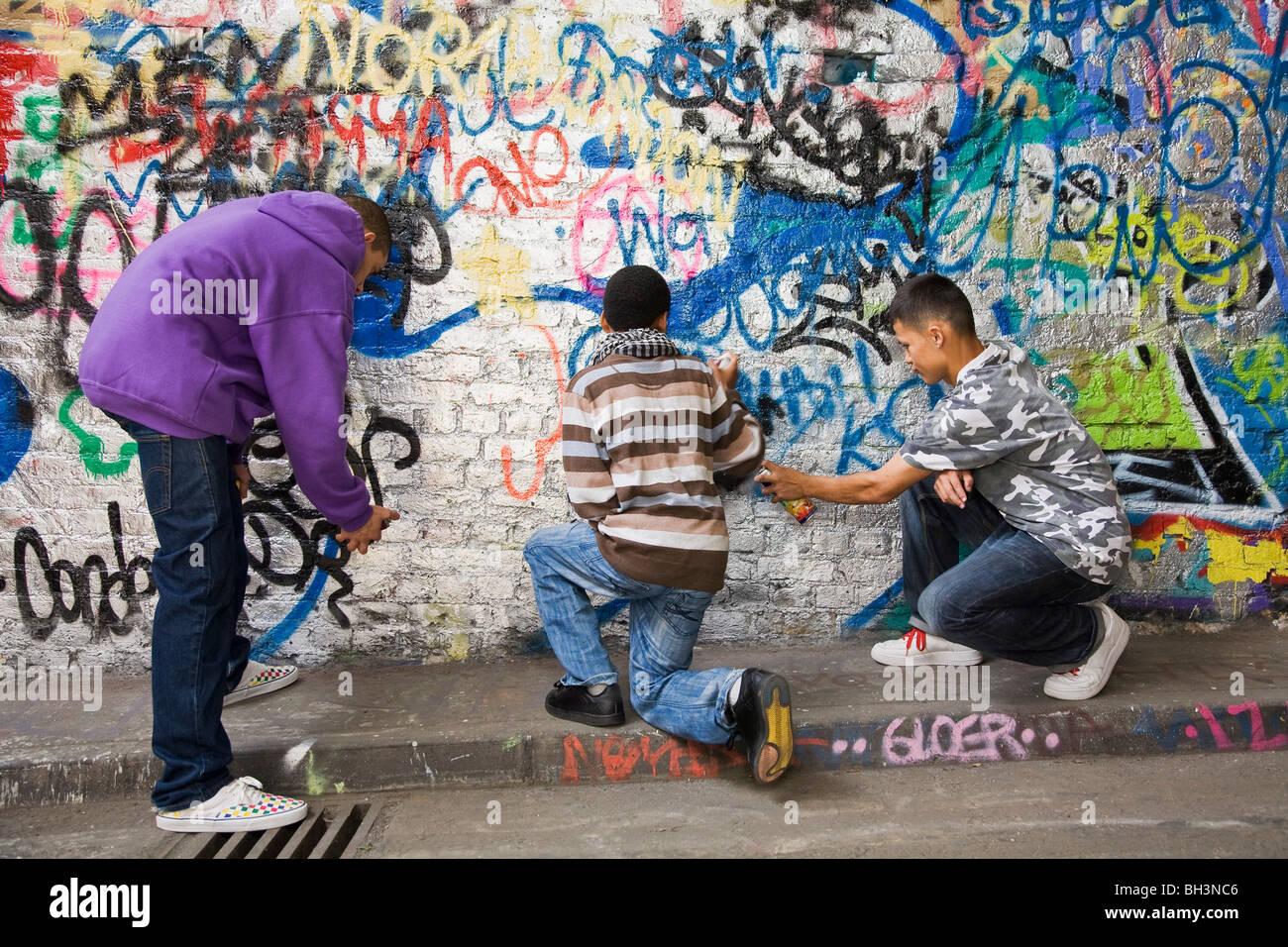 U2 graffiti wall location - Teenage Gang Doing Graffiti On A Wall Stock Image