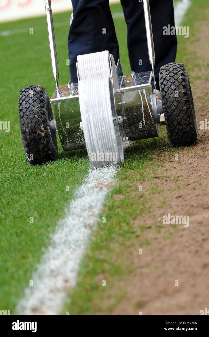 Groundsman putting a white line down a football pitch for White line marker paint