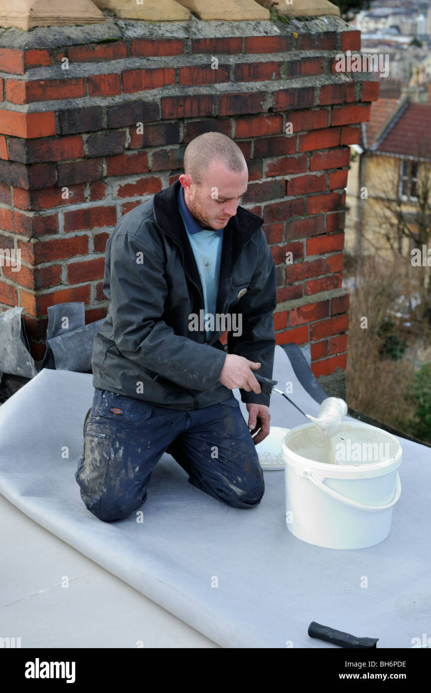 Roofer spreading adhesive for new EPDM rubber roofing membrane on