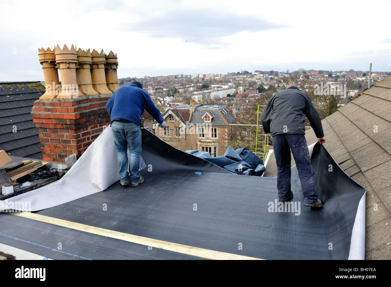 Roofers Repairing Flat Roof With New EPDM Rubber Membrane On House