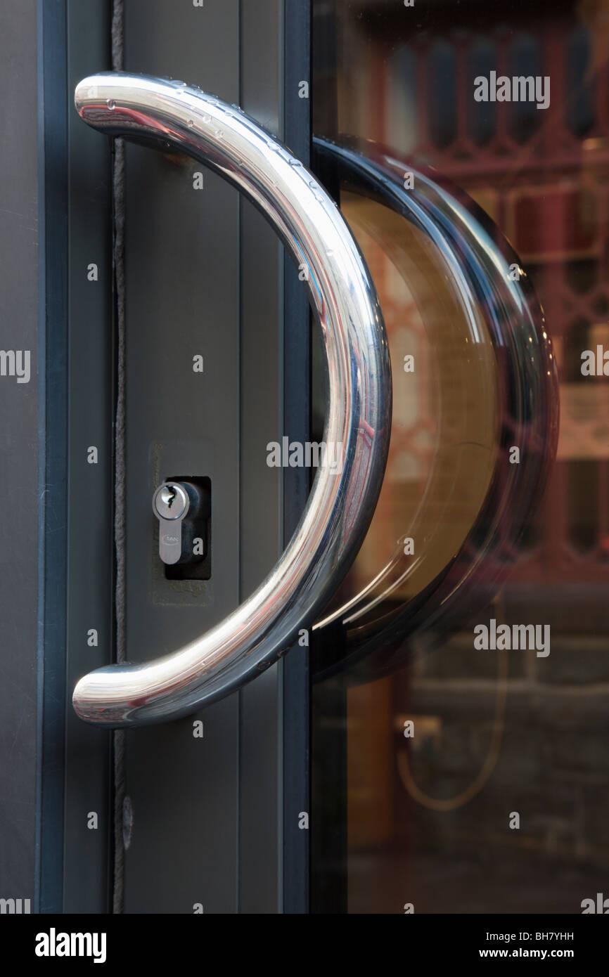 Decorating circular door images : Close-up of a semi-circular chrome handle and keyhole on a glass ...