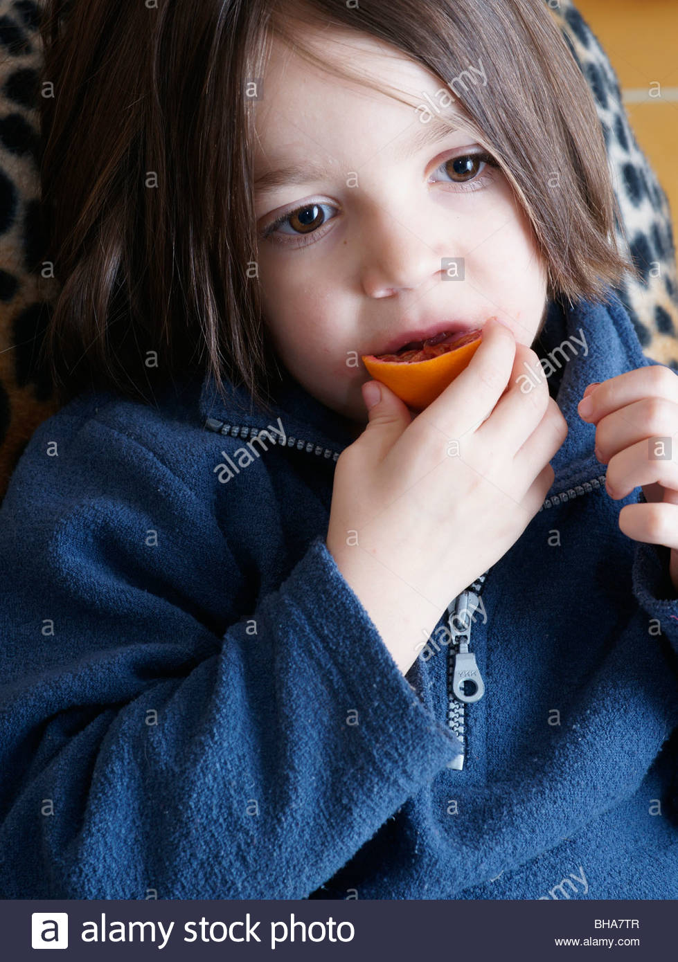 kids watching tv and eating. child children kid boy kids watching tv eating a slice of orange fruit kids and w