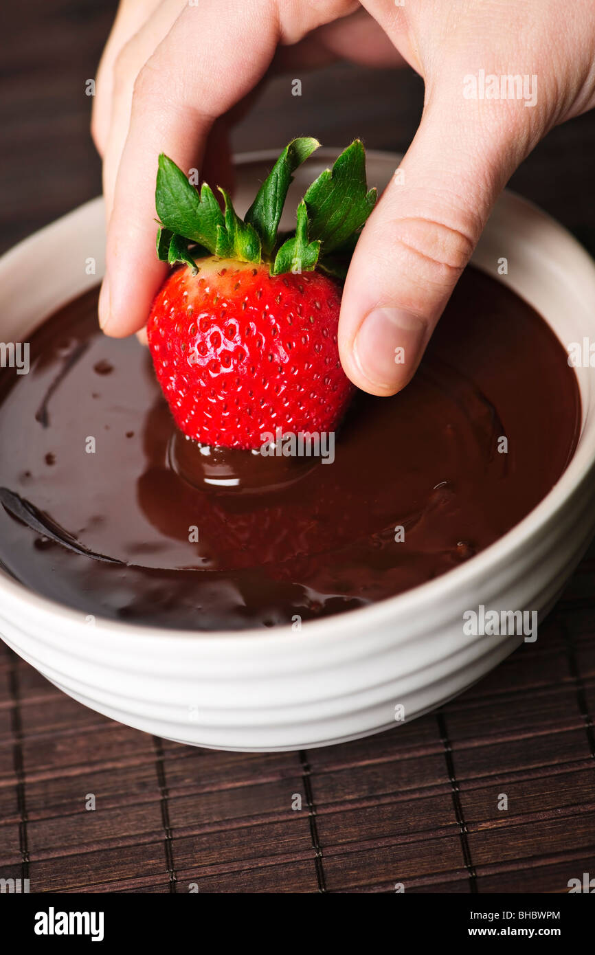 Hand dipping fresh strawberry in melted chocolate Stock Photo ...