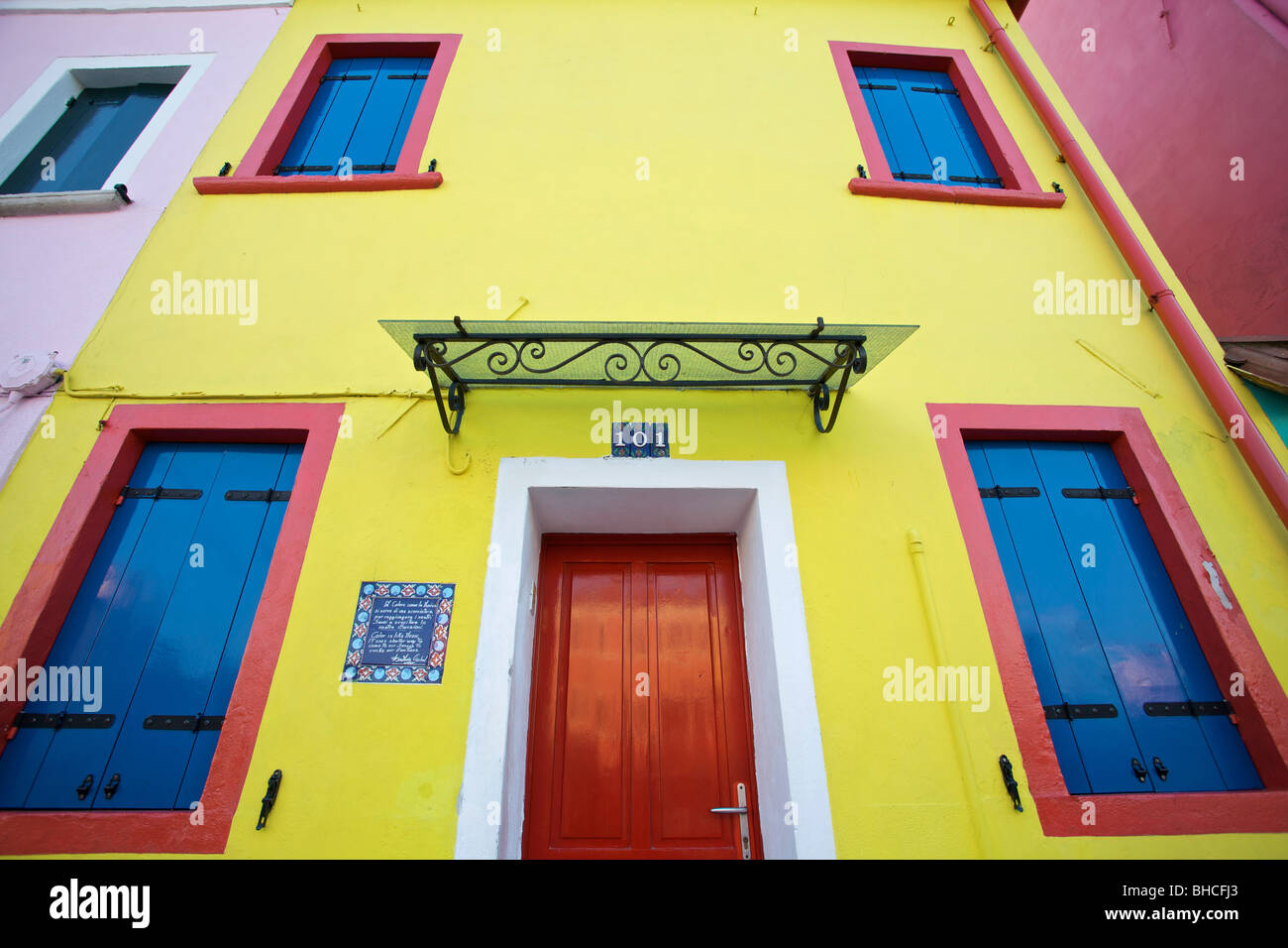 A bright yellow house with red and blue windows burano for Yellow and red house