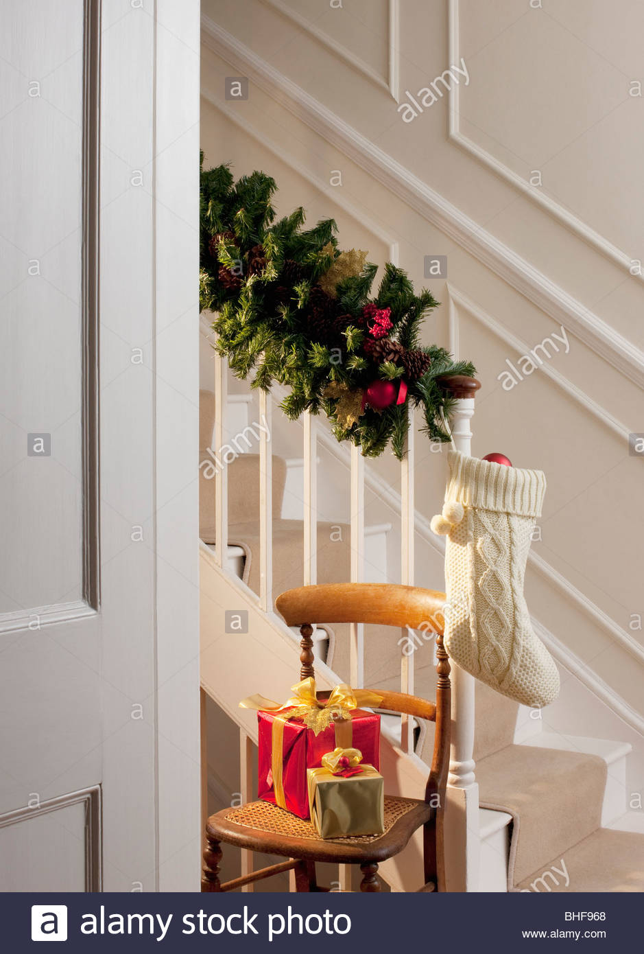 Christmas gifts and stocking near staircase stock photo for Hang stockings staircase