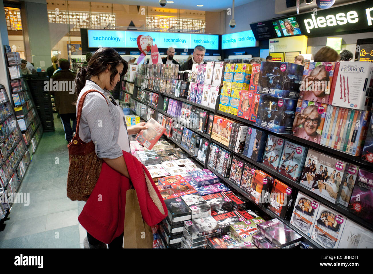 A teenage girl looking at Blu Ray DVD DVDs Interior  the HMV shop   Bluewater shopping mall  Kent UK. A teenage girl looking at Blu Ray DVD DVDs Interior  the HMV shop