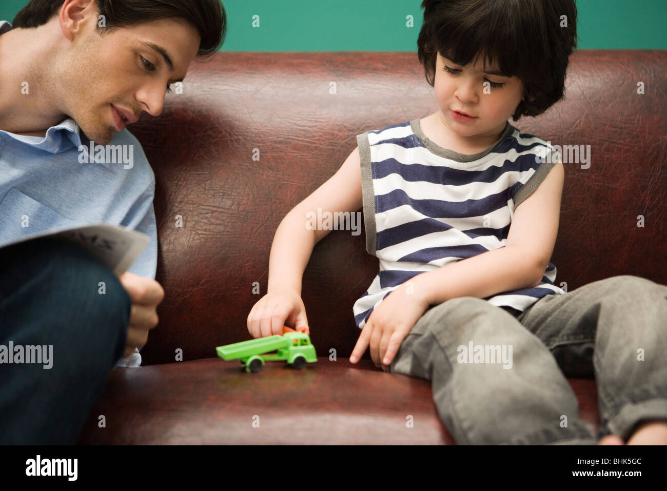 Boy Toys For Dads : Little boy sitting on sofa with father playing toy