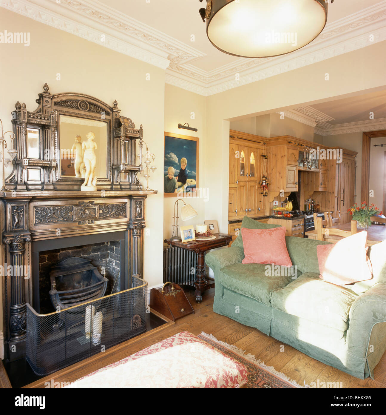Cast Iron Over Mantel Mirror And Fireplace In Open Plan Traditional Living Room Kitchen Dining