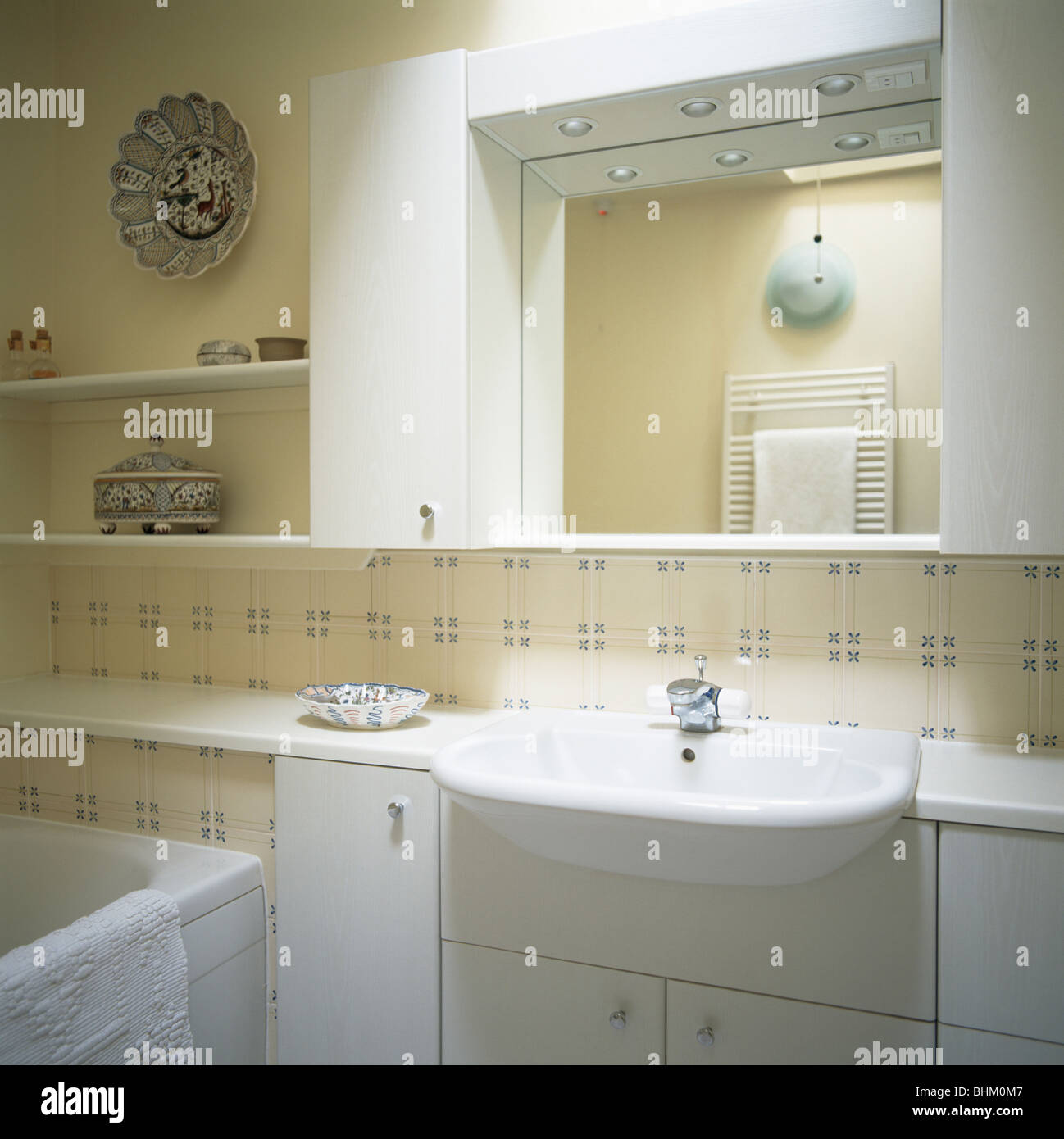 Mirror above basin in fitted vanity unit in modern bathroom with patterned  cream Fired Earth tiles. Mirror above basin in fitted vanity unit in modern bathroom with