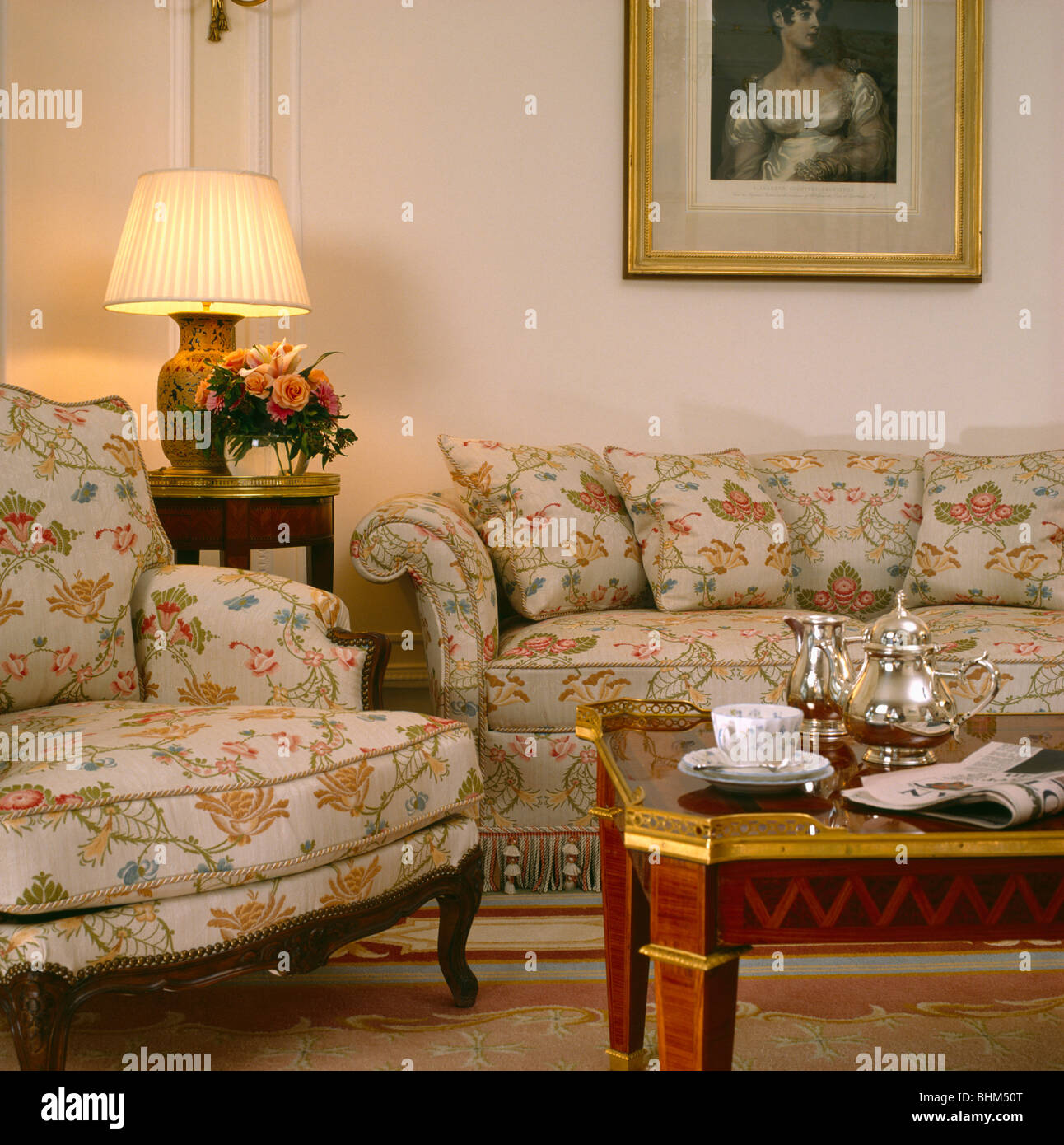 Lighted lamp on small table between floral patterned sofa and ...