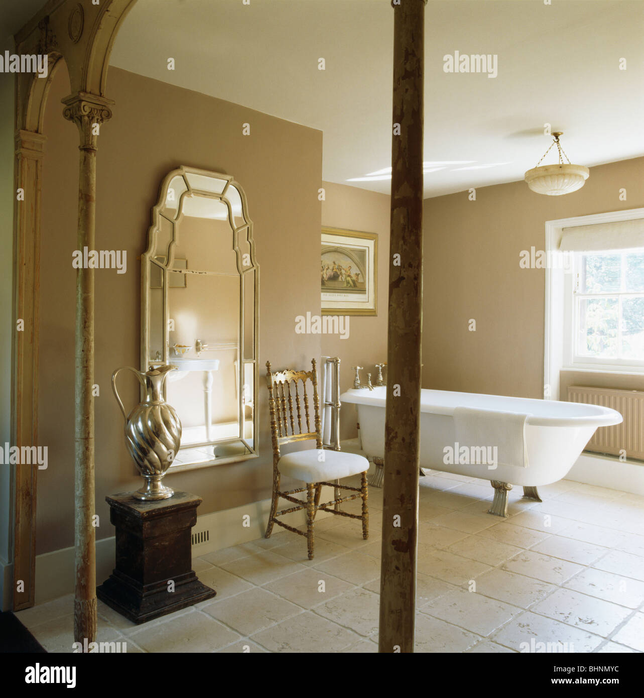 Large Venetian Mirror And Roll Top Bath In Beige Bathroom With Limestone Tiled Floor