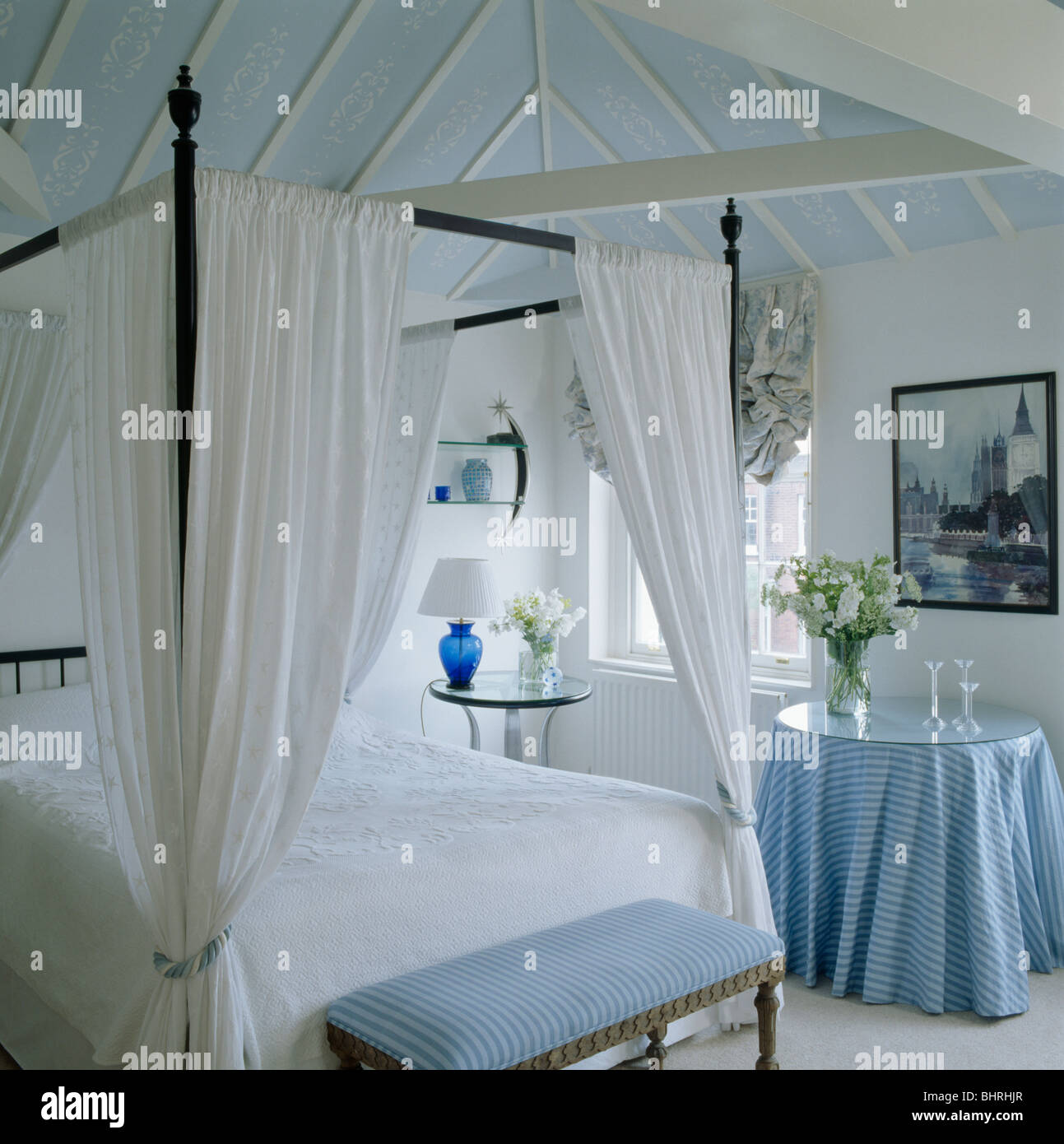 Simple four poster bed with white drapes in white bedroom with blue stool  and small table with blue cloth below blue ceiling. Simple four poster bed with white drapes in white bedroom with