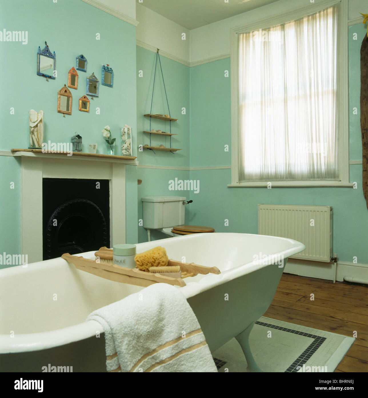 Roll top bath with wooden bath rack in pale green bathroom with small white  fireplace and voile curtain on window. Roll top Bath With Wooden Bath rack In Pale Green Bathroom With