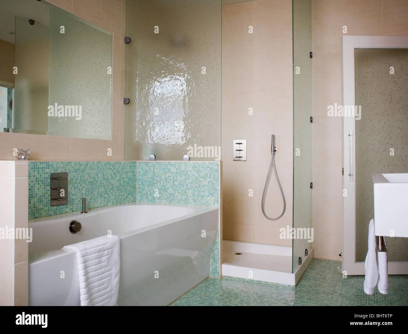 green mosaic tiles above bath in modern bathroom with walk i