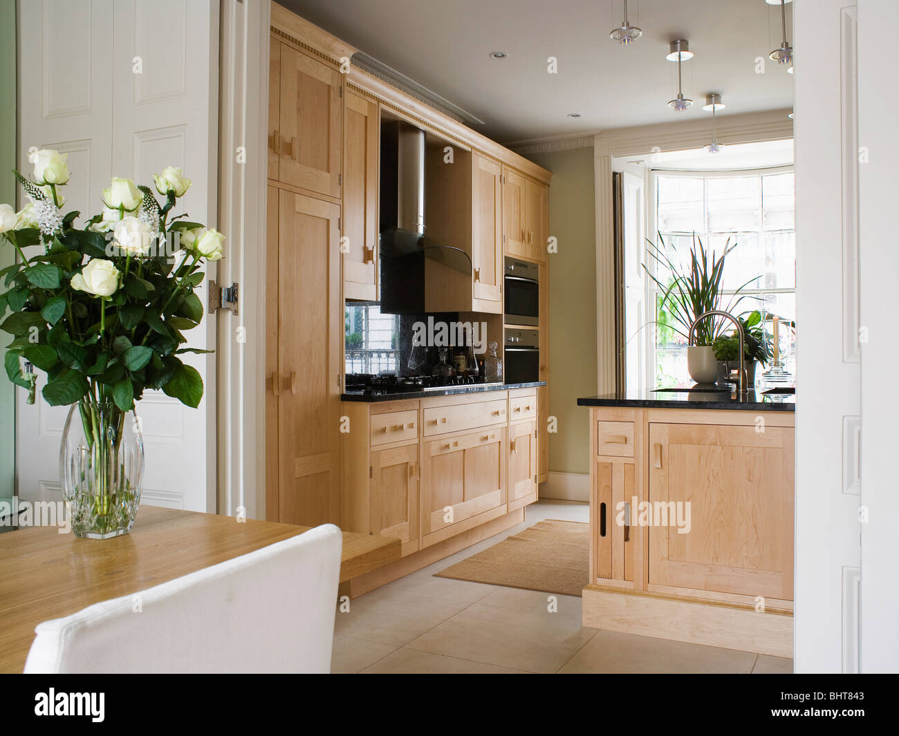Dining Room With Double Doors Open To Modern Kitchen Pale Wood Units