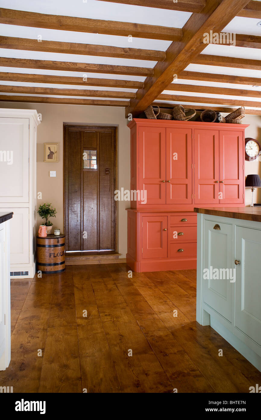 Large red cupboard in country kitchen with wooden floor-boards and ...