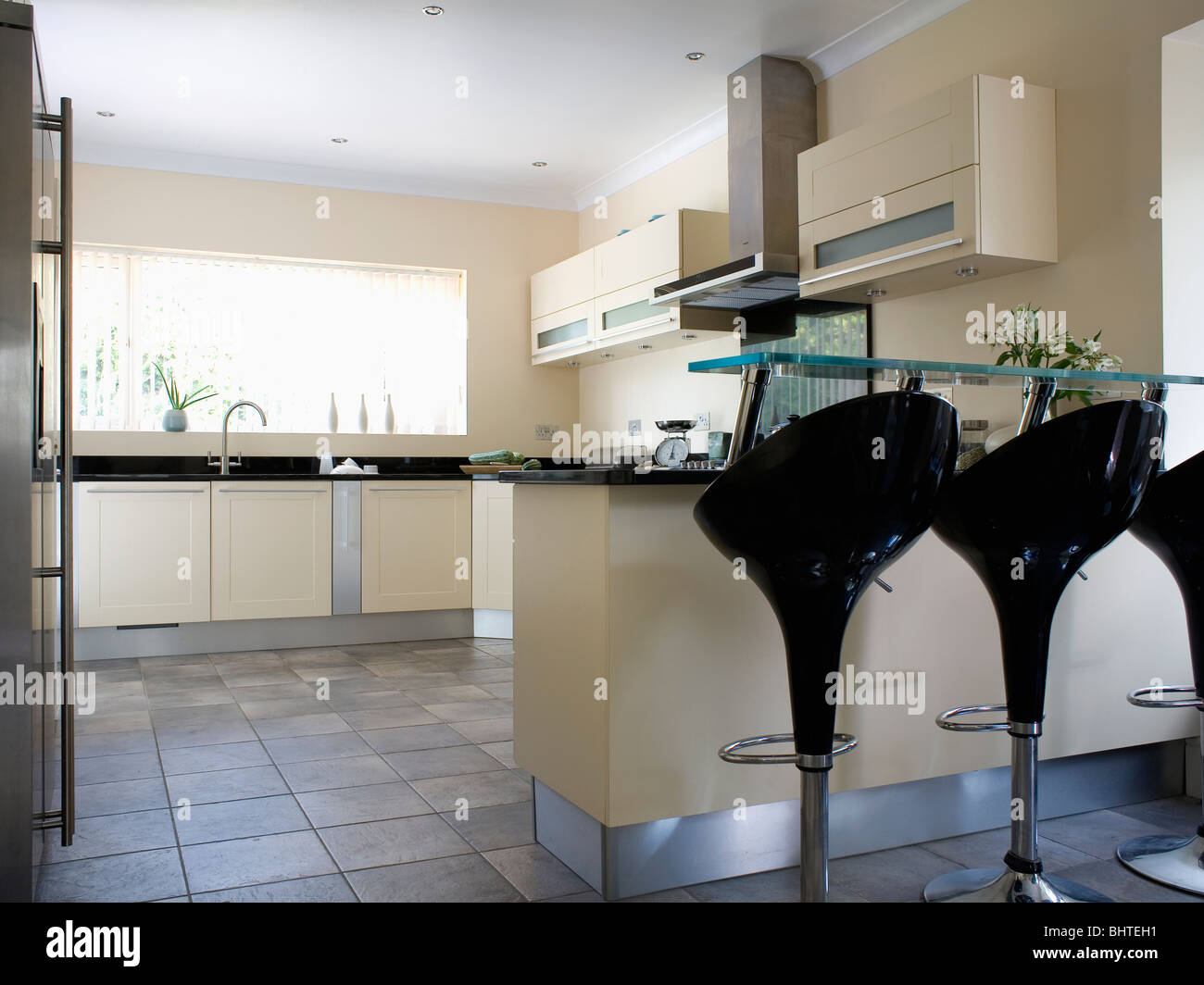 Black Bombo Stools At Breakfast Bar In Modern Kitchen With
