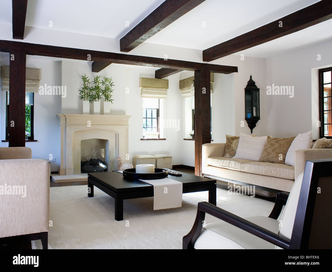 Beige Sofa And Large Black Coffee Table In Modern White Cottage Living Room  With Stone Fireplace And White Carpet Part 65