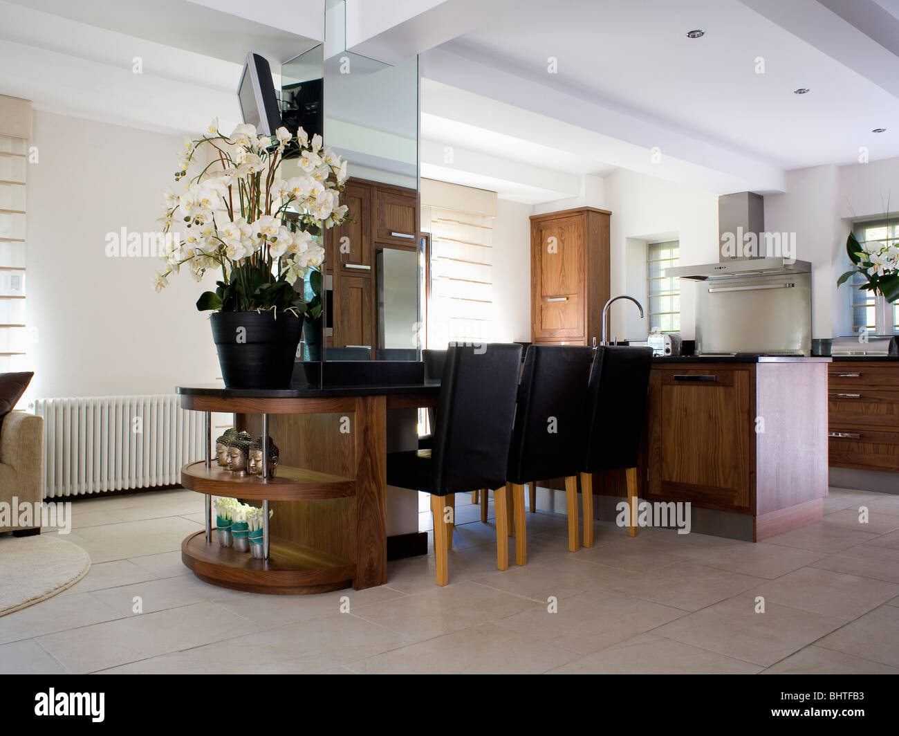 Tall Cream Orchids In Pot On Mahogany Unit Large Modern Kitchen Dining Room With Mirrored Wall And Limestone Flooring