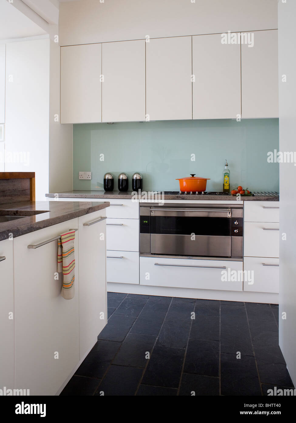 Black floor tiles in modern white kitchen with glass splash back black floor tiles in modern white kitchen with glass splash back behind stainless steel oven dailygadgetfo Image collections