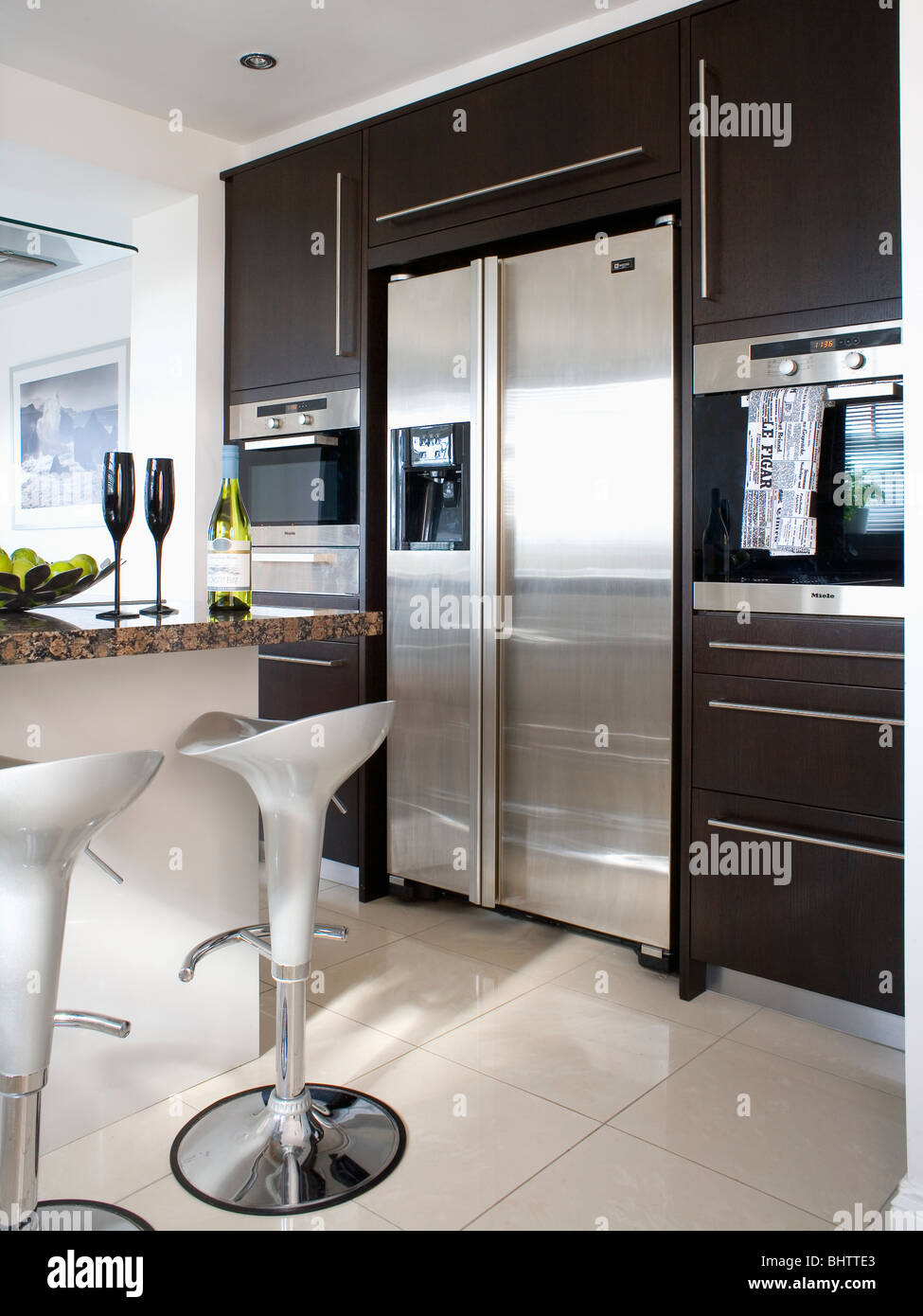 Steel Bombo Stools In Modern Kitchen With Large American Style Stainless  Steel Fridge Freezer In Tall Black Fitted Unit