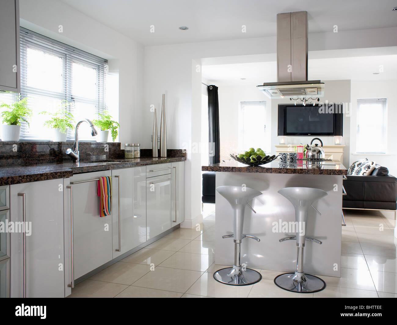 Metallic Grey Bombo Stools At Breakfast Bar On Island Unit In Modern White  Open Plan Kitchen