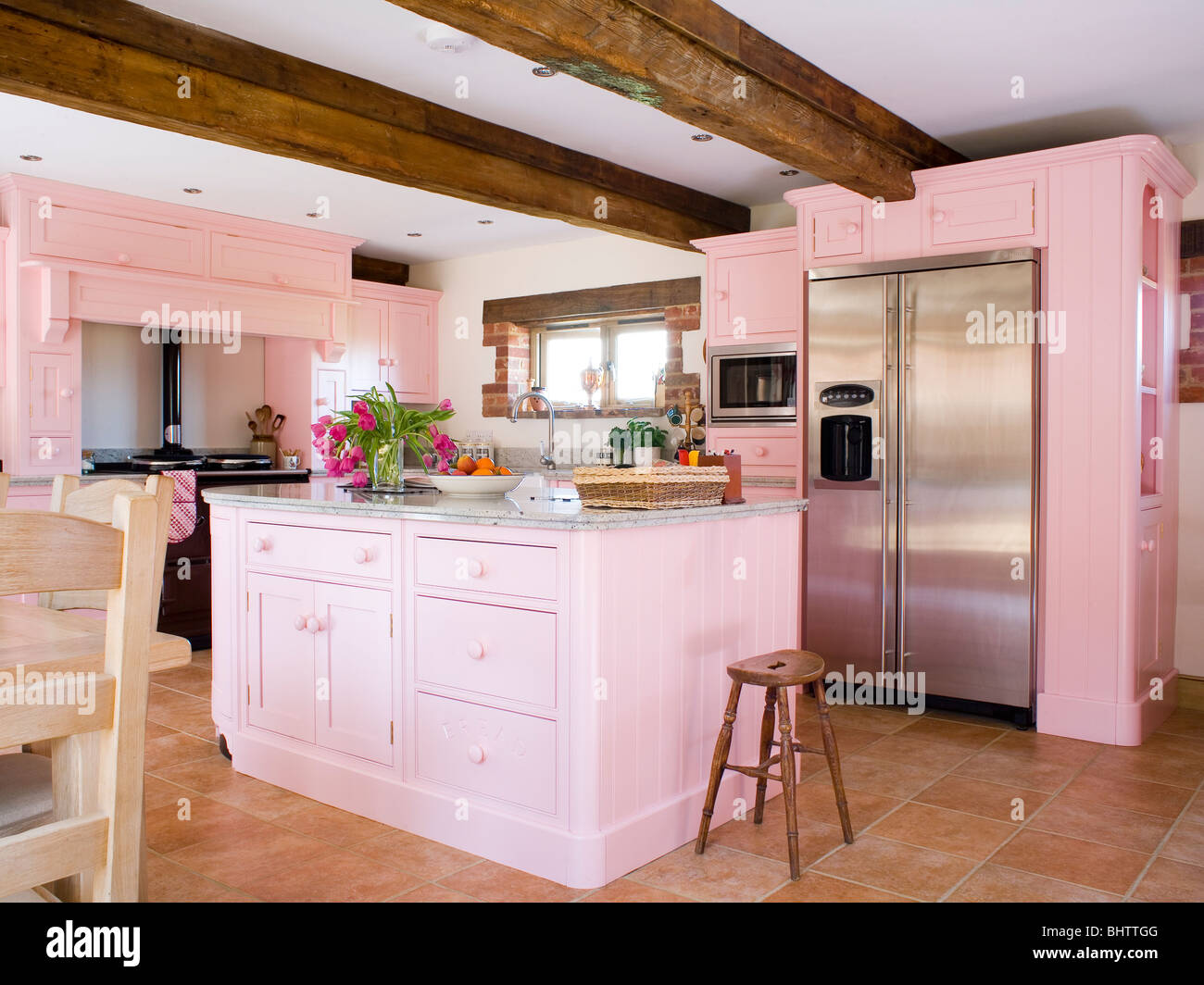 Pastel Pink Fitted Units And Island Unit In Country Kitchen With Stock