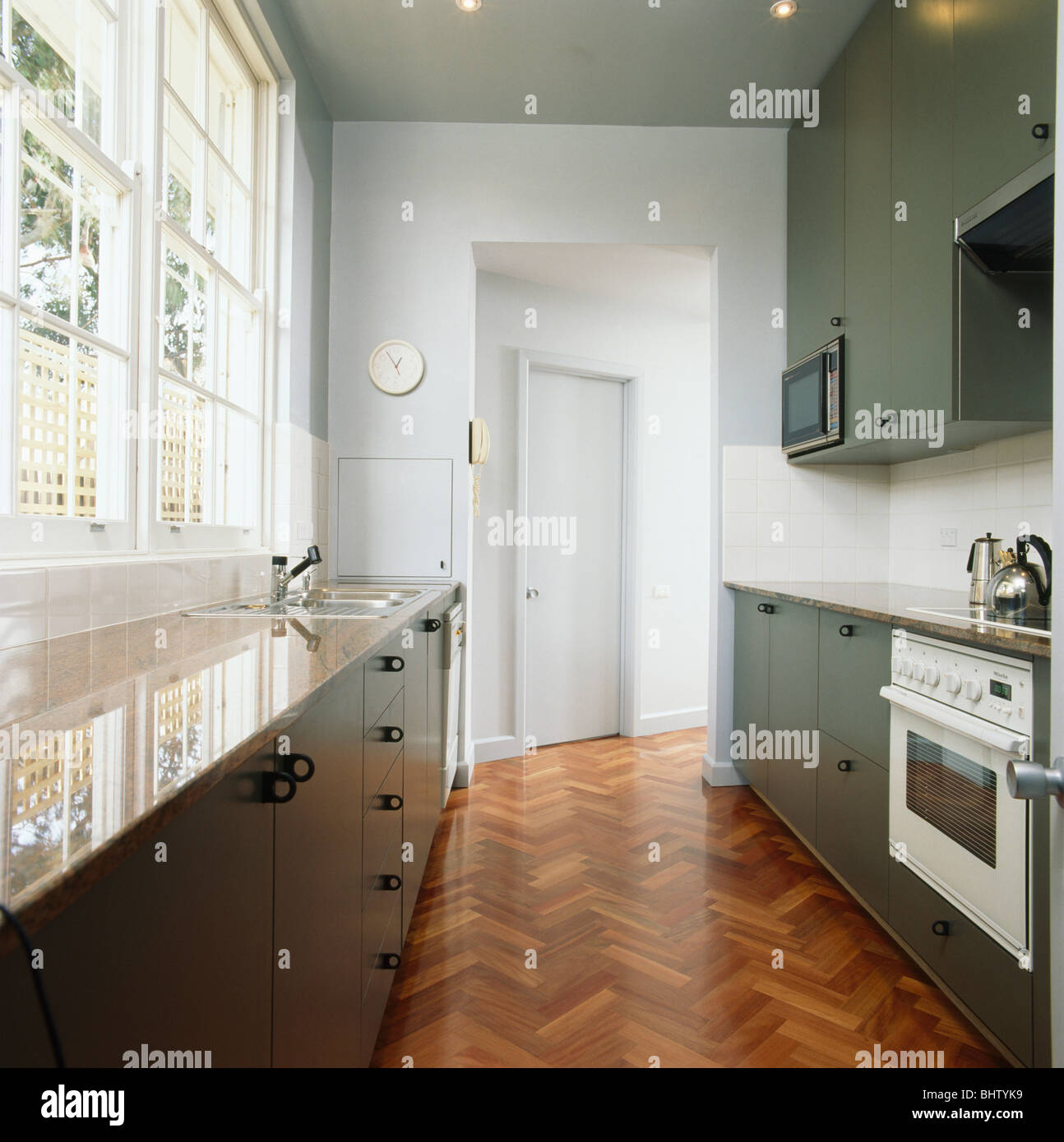 White galley kitchens - Parquet Flooring In Modern White Galley Kitchen With Gray Fitted Units And Granite Worktops