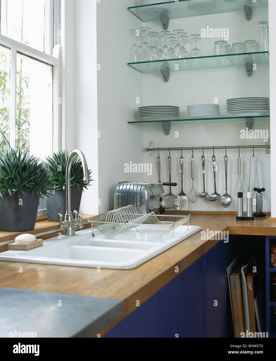 Modern kitchen shelves - Double White Sink Below Window In Modern Kitchen With Glass Shelves Above Steel Utensils On Metal Storage Rack