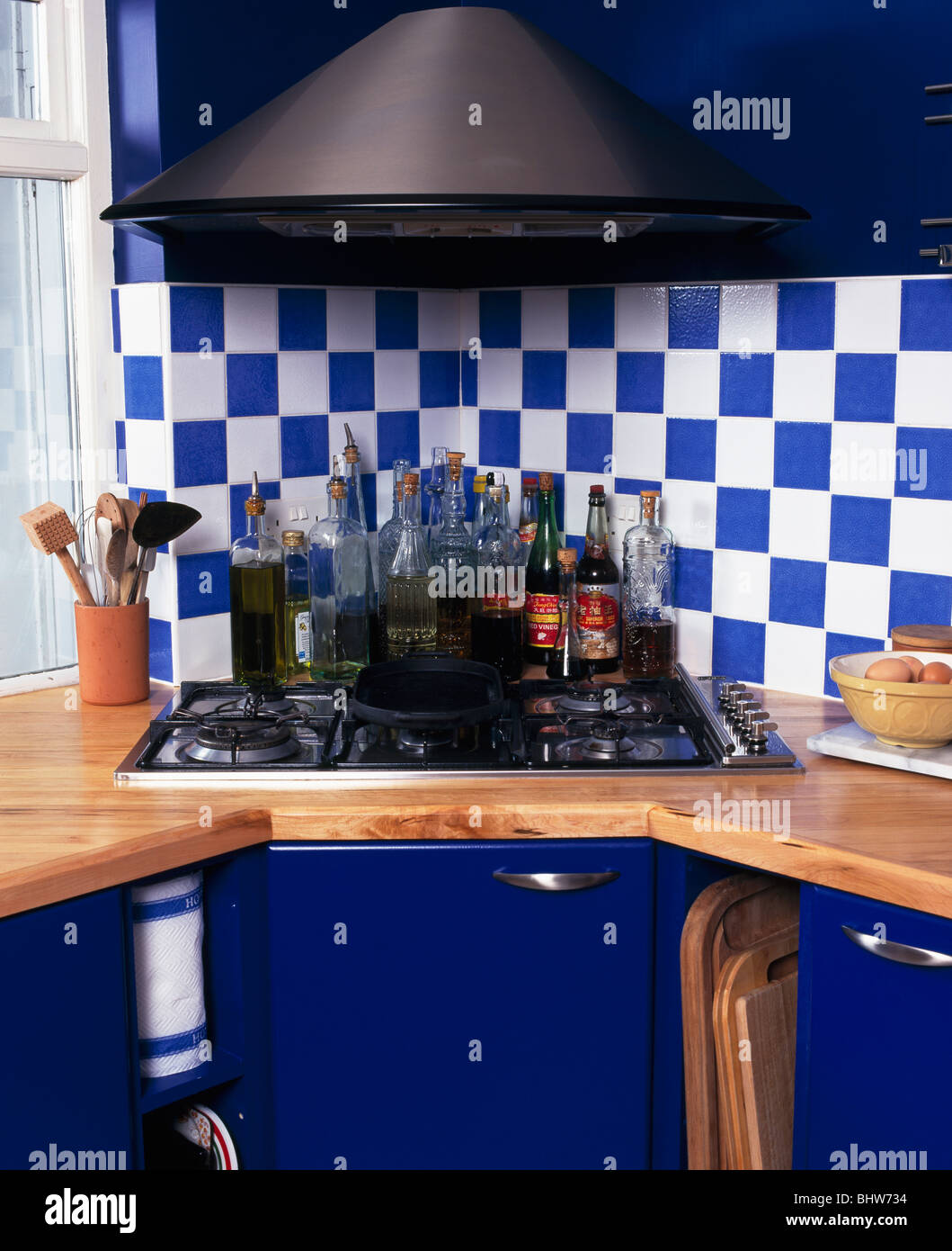 Blue+white wall tiles above corner-set hob in wood worktop ...