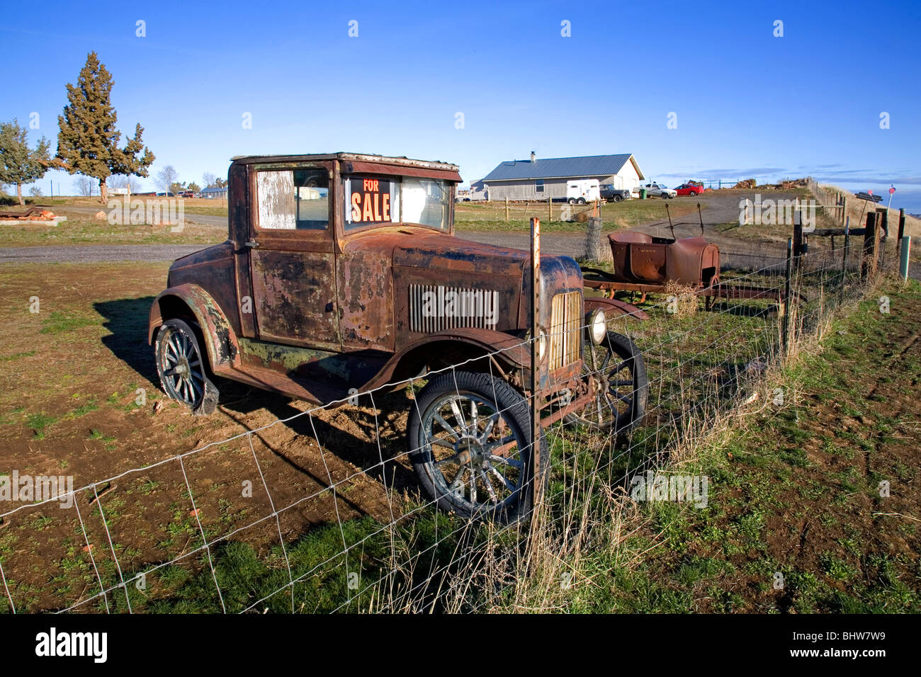 A For Sale sign on a rusty antique classic old car in a field in ...