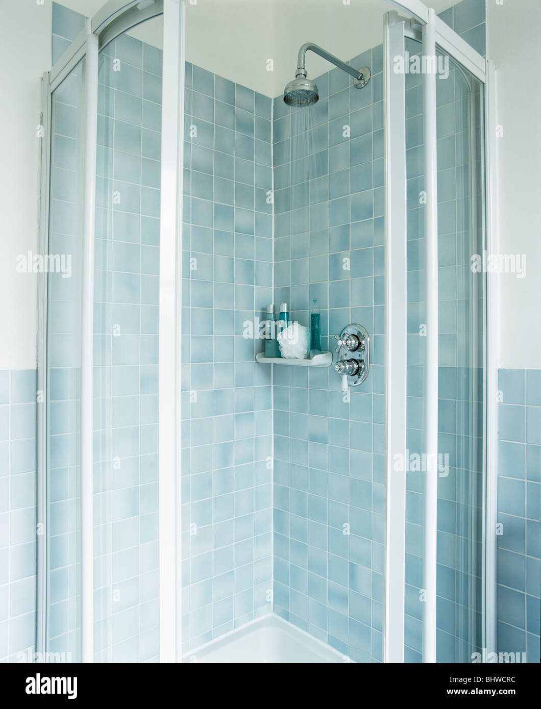 Pale blue tiled shower cabinet with glass doors in modern bathroom ...