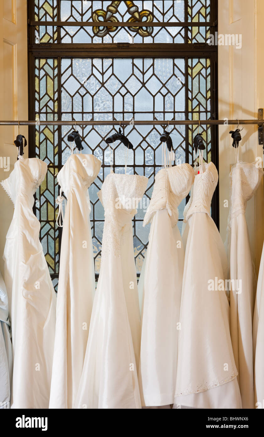 A row of wedding dresses hanging on a clothes rail stock for Wedding dress shops in oklahoma city