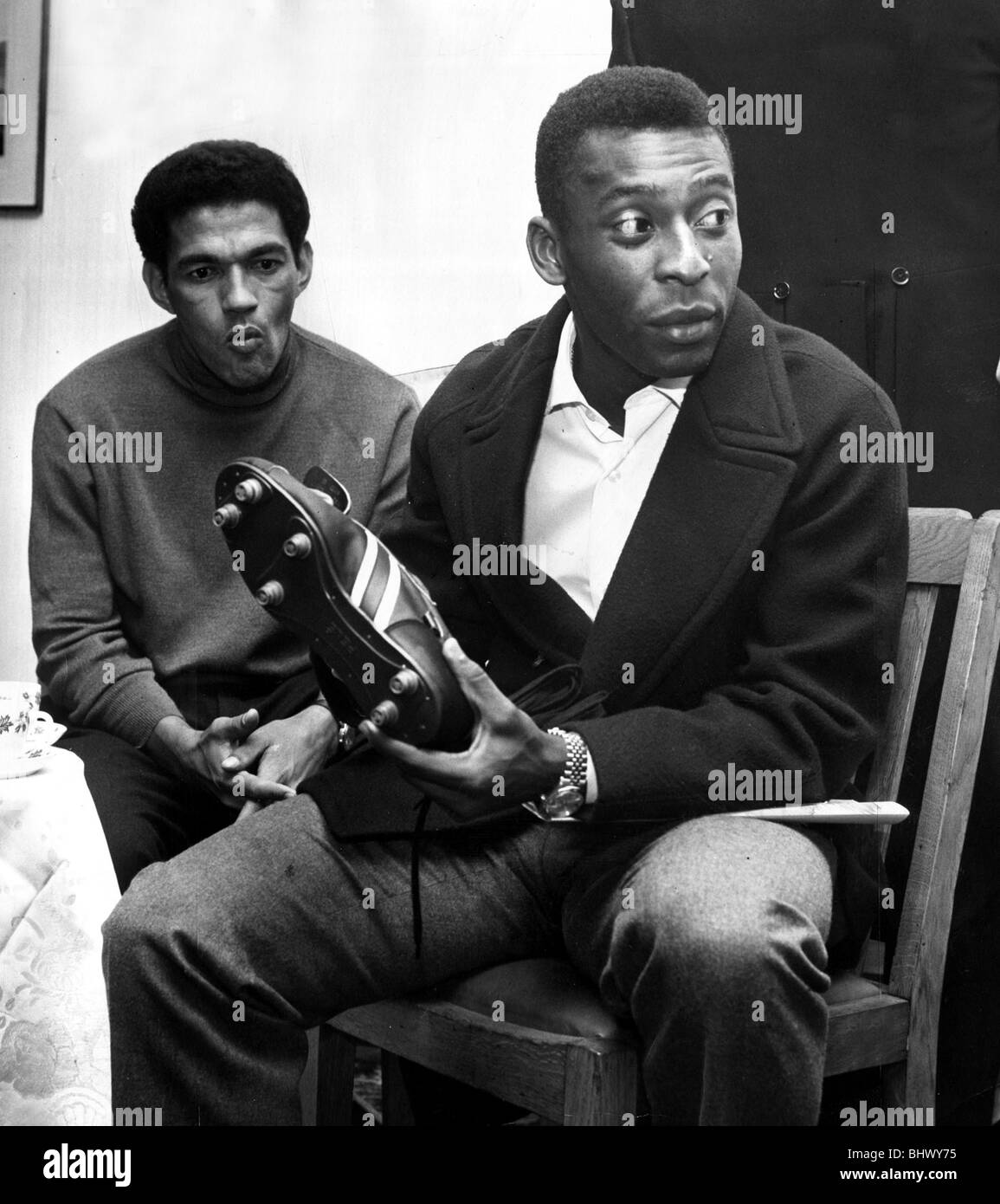 Brazilian football star Pele looking at a pair of football boots