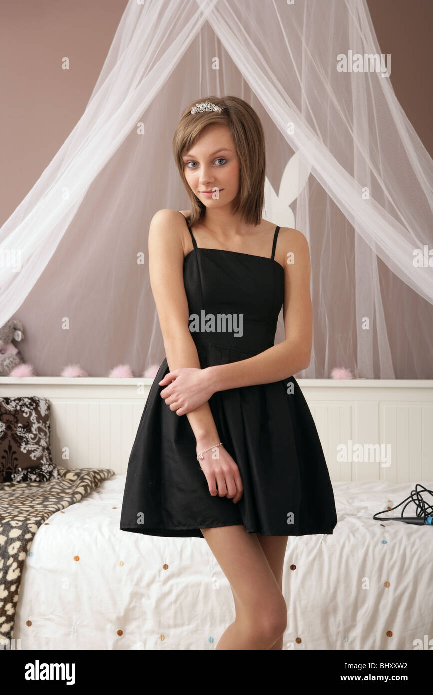 Fourteen year old girl standing in her bedroom wearing a black dress and  tiara. Fourteen year old girl standing in her bedroom wearing a black