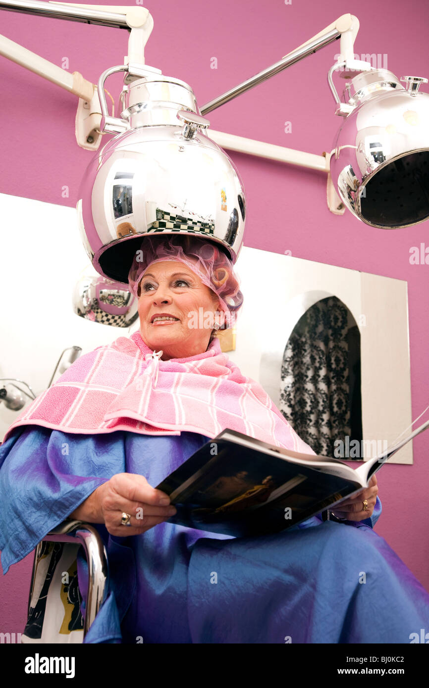 Portrait Of Mature Woman Sitting Under Hair Dryer At Hair